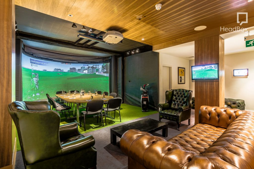 A golf bunker with an interactive golf screen on the back wall. A meeting room table and large chesterfield sofas.