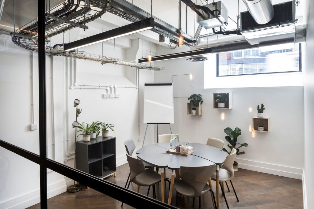 Meeting room to hire in London with green plants, white walls and modern furnishings
