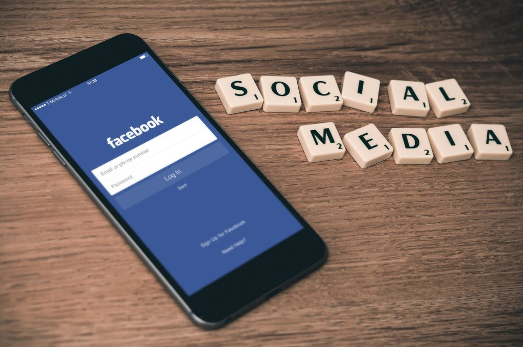 a phone had been laid onto a wooden table with the facebook login page open on the screen. Next to the phone are scrabble pieces that read out 'Social Media'