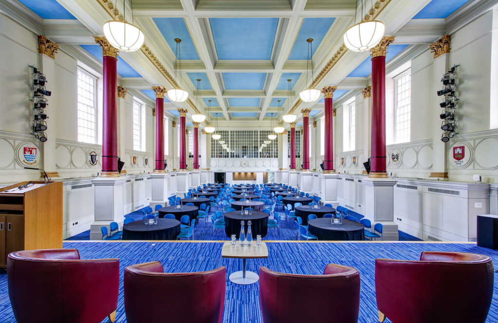 the great hall at BMA House has bright blue flooring and red chairs in a theatre style set up