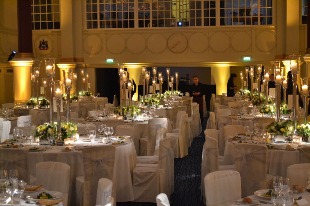 the great hall at BMA House set up for a dining event with large candles on the tables and the table tops and chairs draped in cloth