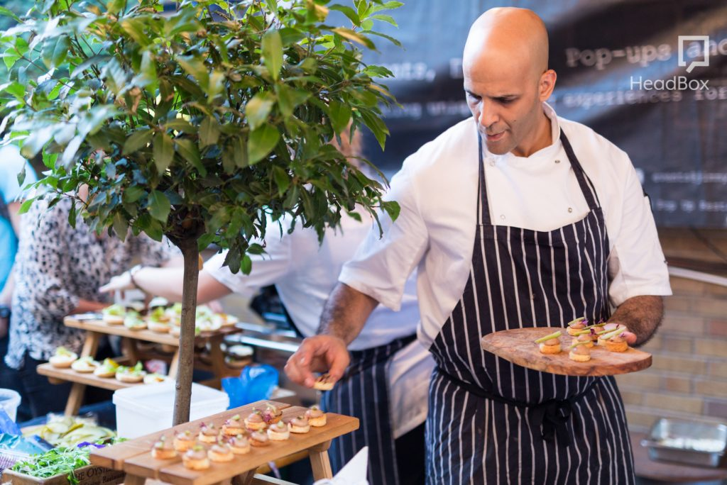 a man in a white shirt and blue and a white striped apron is setting up canapes onto a wooden table. There is a large green plant behind him in the background of this corporate event venue.
