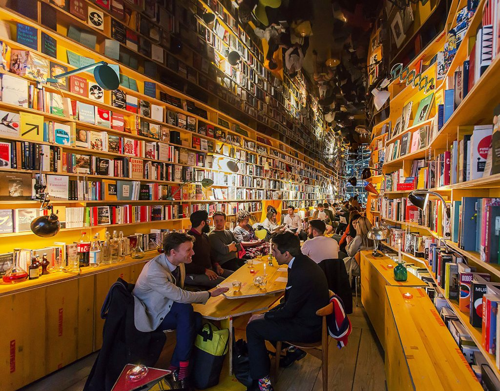 the inside of Libreria London, an east london bookshop shows interior walls stacked top to bottom with books. There's a table set up in the middle of the room with people sitting around it in conversation