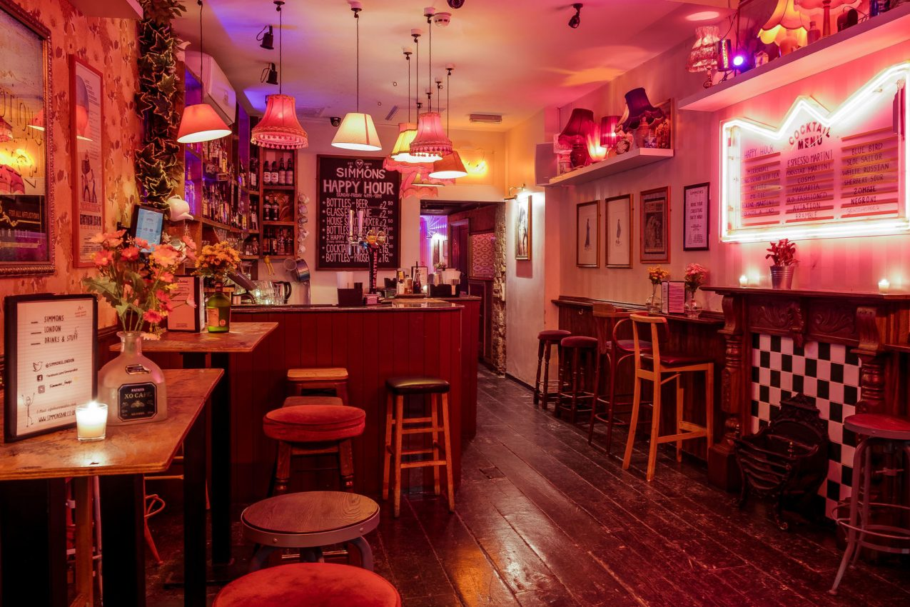 A bar with dim pink lighting, high bar stools and low hanging lights.