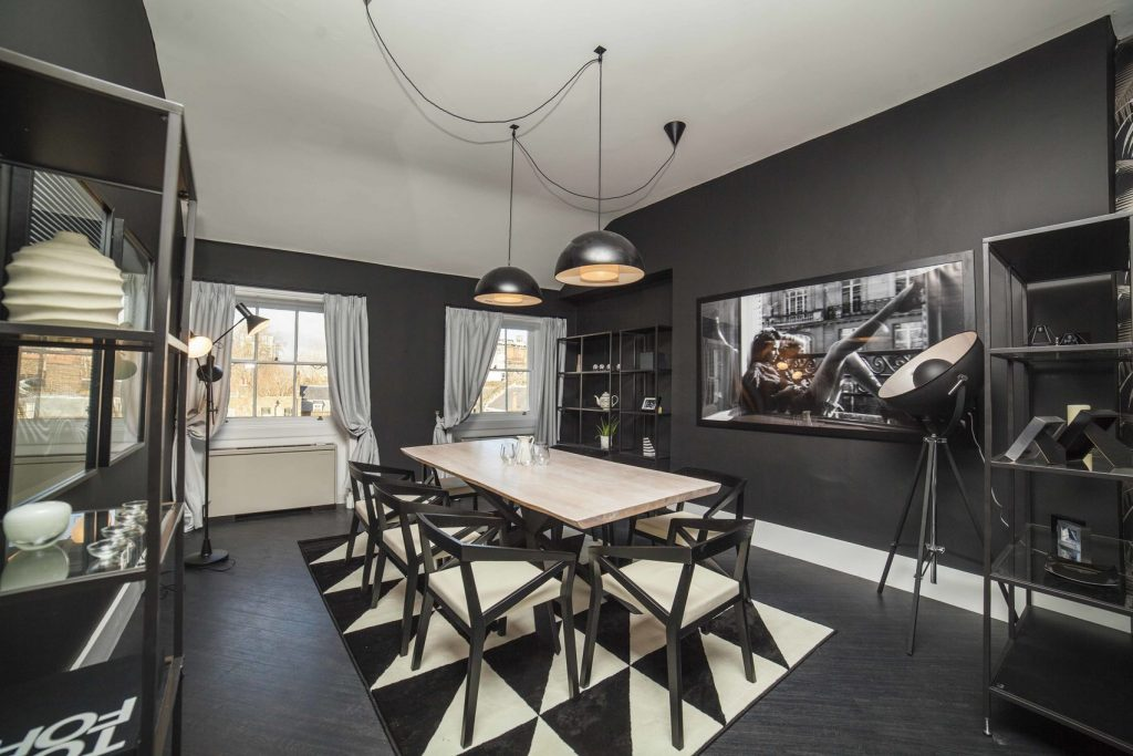 A stylish boardroom with black walls and white and black furnishings. The perfect venue hire London