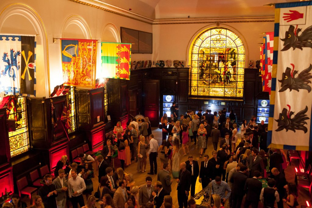 Stationer's Hall is set out for a standing drinks reception. The room still has flags draped from the walls and dark wooden panelling. There is also people stood in the middle of the room talking.