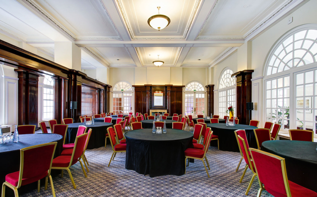 the paget room at BMA House has black table cloth covering all the tables with red chairs pushed around them in cabaret style