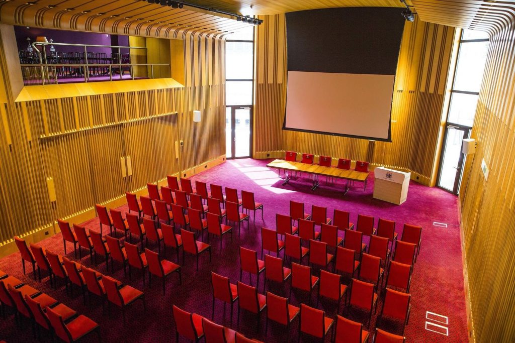 Salters' Hall is a great hall to hire in London for conferences or networking. The Space has high dramatic ceilings and is set out in conference style with the chairs facing the back wall which has a TV on it and a table underneath.