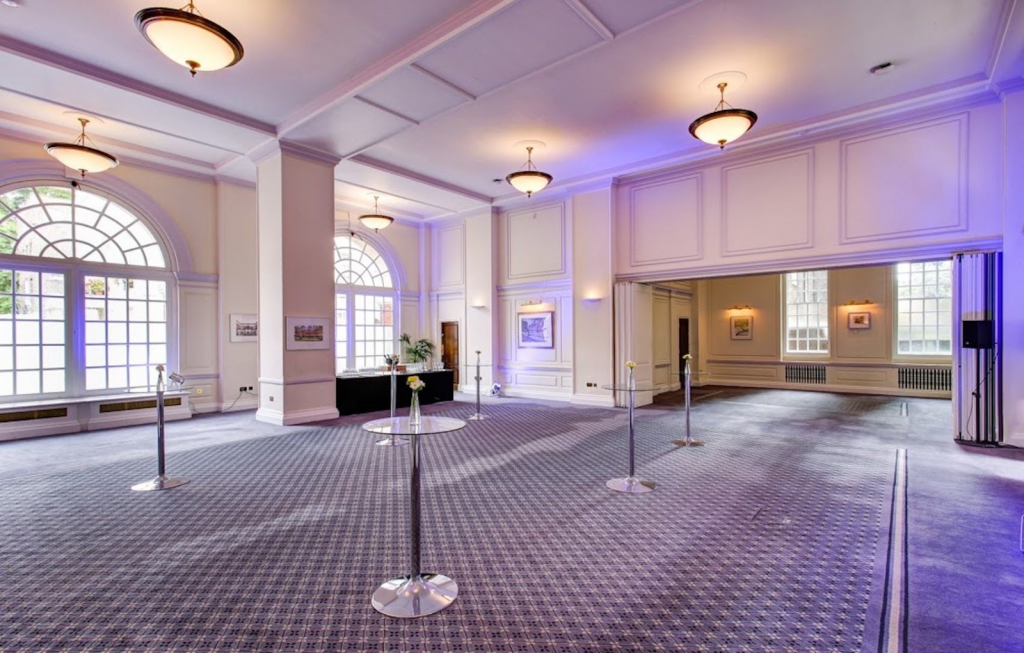 the snow room at BMA House is a white walled room thats set up for a standing drinks reception with tall tables dotted around the event space