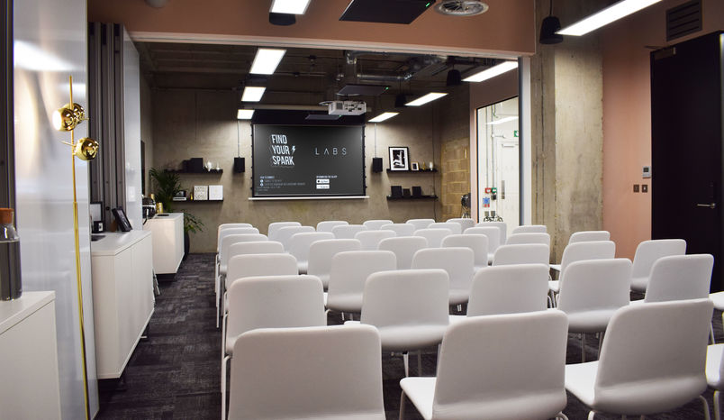 A small conference room with white chairs
