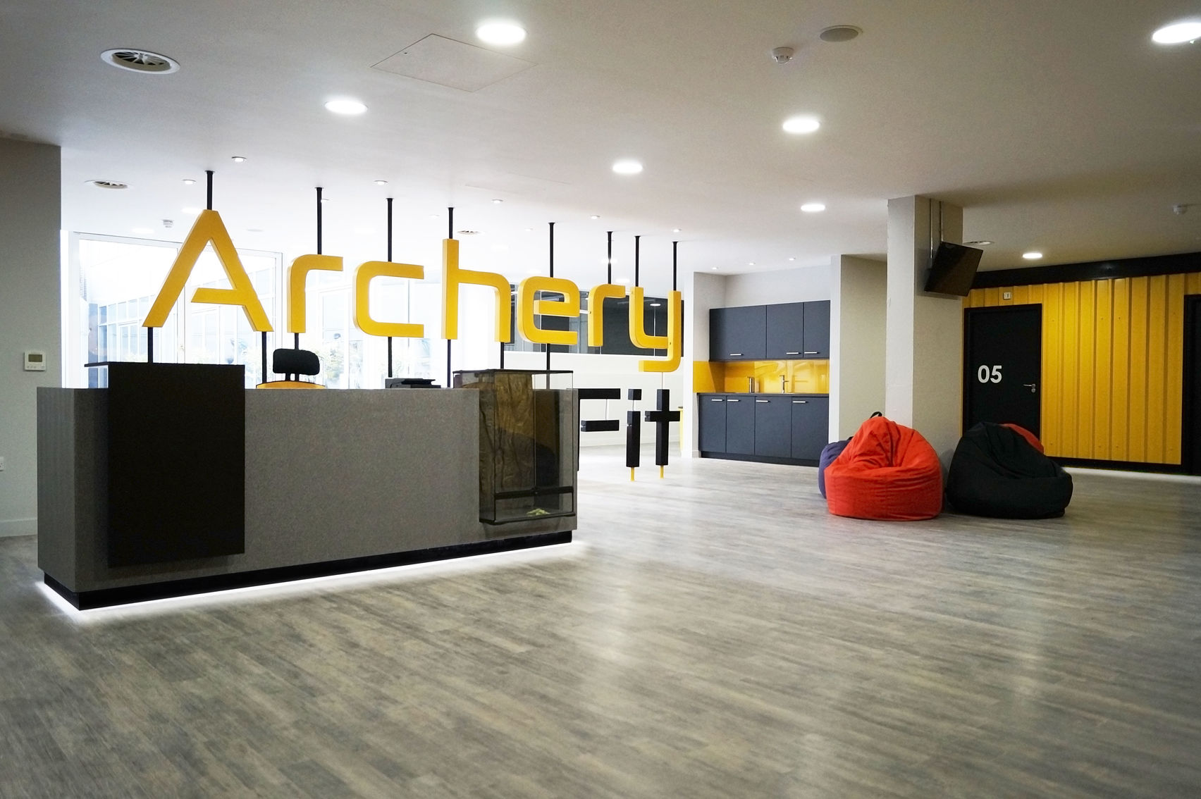 Archery Fit is a great corporate away days venue. The space is a large reception area which has a large archery sign in yellow above the desk. On the right hand side there are several bean bags on the floor then behind that a small kitchen area.