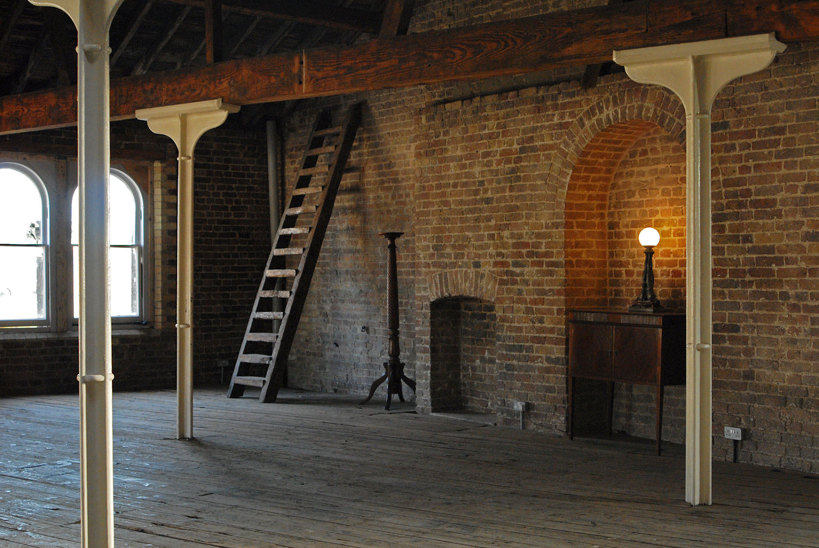 a large event space at menier space with exposed brick walls and a lamp at Menier Spaces