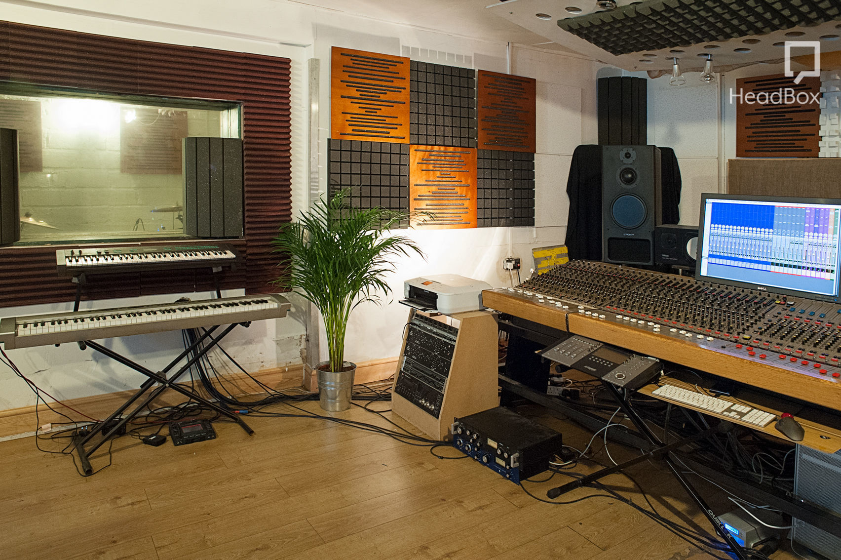 A recording studio in London which has a mixing deck and computer screens. On the left hand side of the studio there is a double keyboard which faces the vocal booth window. There is soft lighting and a green grassy plant next to the keyboard