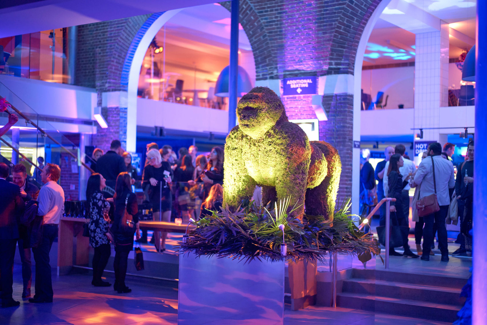 The space is of the terrace at ZSL. A large event space with arched walls and high ceilings. The room is full of people but the focus point is the gorilla in the middle which is lit up in yellow light.