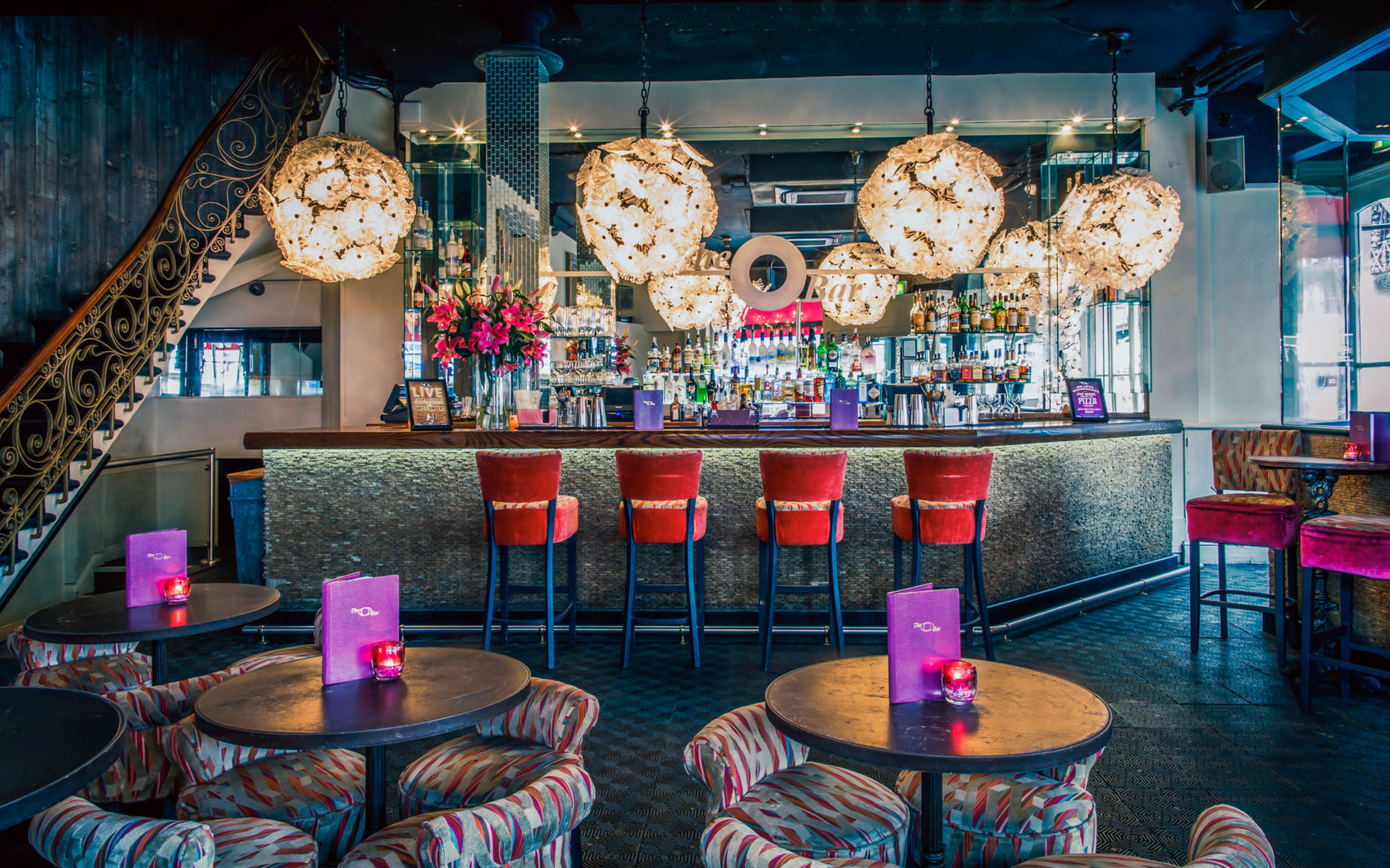 A bar with red chairs and large circular lights