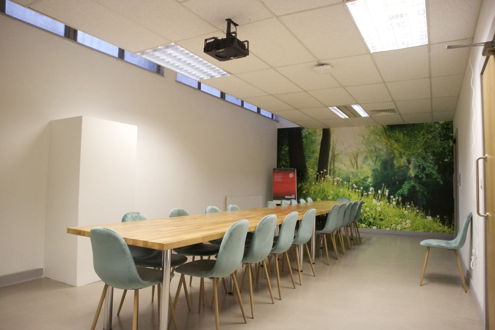 a meeting room with feature wallpaper on the back wall that has a forest scene with a large wooden table and chairs around it