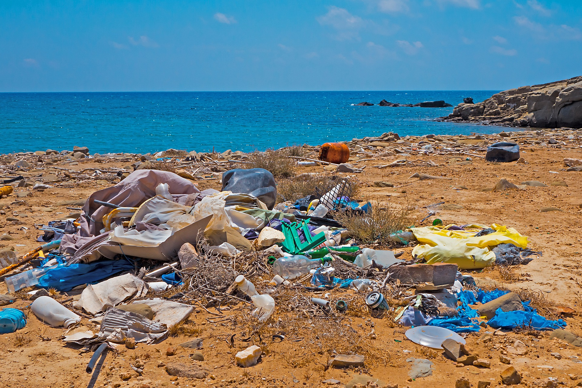 This image is ground level image of lots of plastic that is left on the beach with the sea in the background. There are plastic bags, bottles and rubbish.
