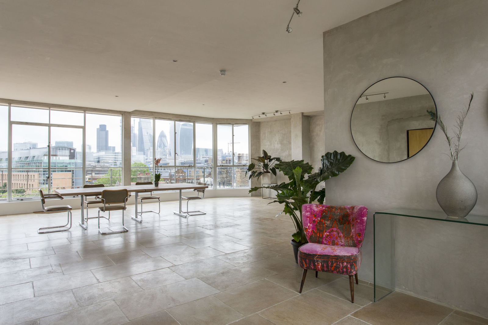 a large white penthouse event space with a large wall window overlooking the city at Menier Spaces