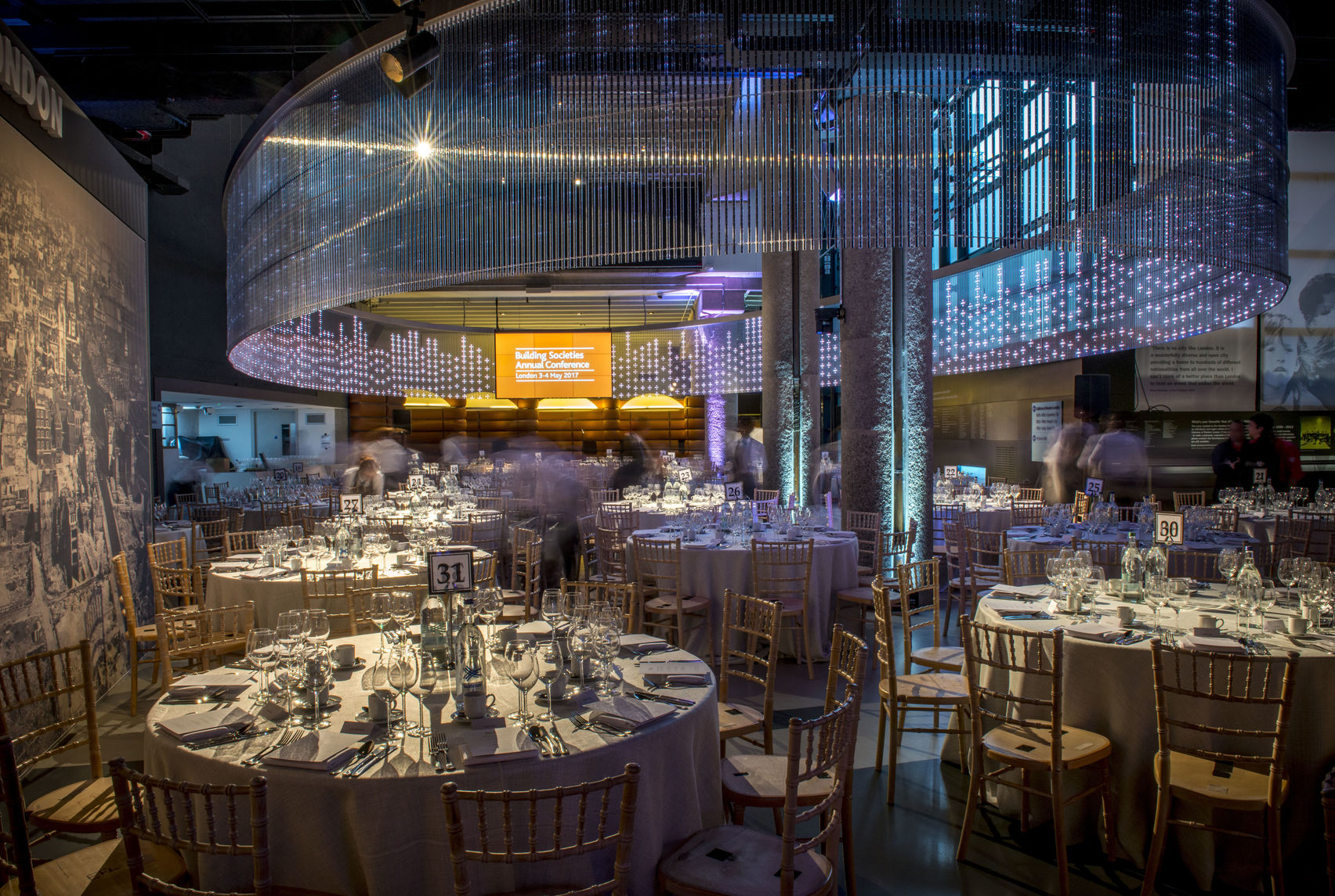 sacklers hall at the museum of london is set up for a cabaret event with large tables and chairs