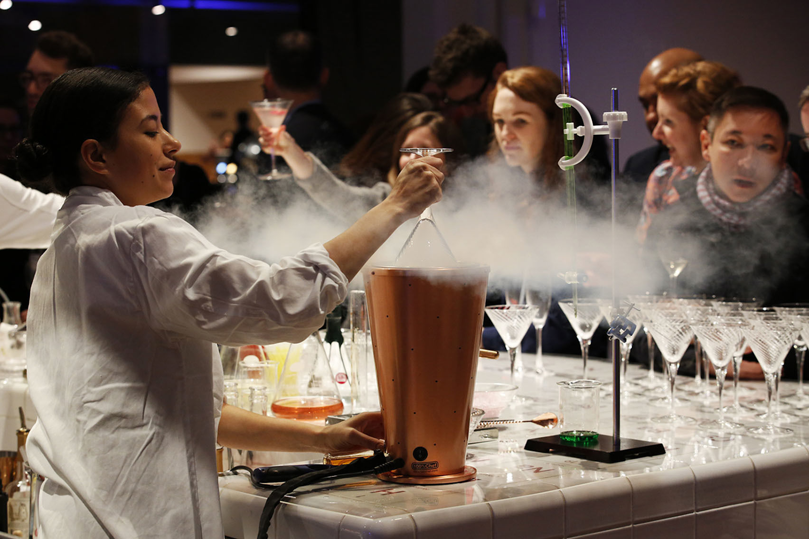 a women dressed in a lab coat is standing infront of a table with smoking flasks - there are people looking at her in amazement