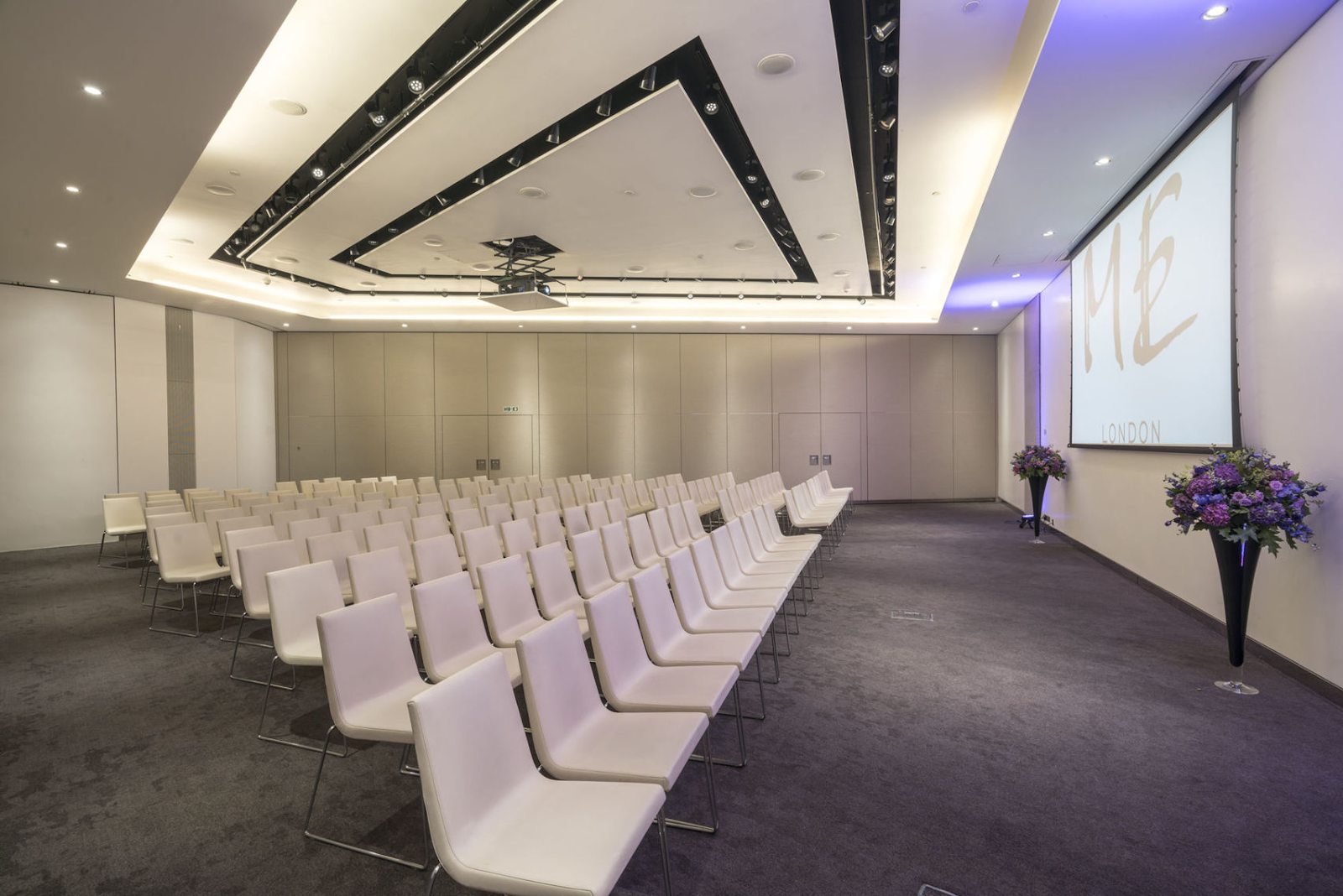 a large white event space with white chairs facing a screen on the wall