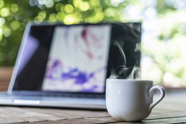 a hot mug of coffee with steam coming off of it, in the background there is an open laptop