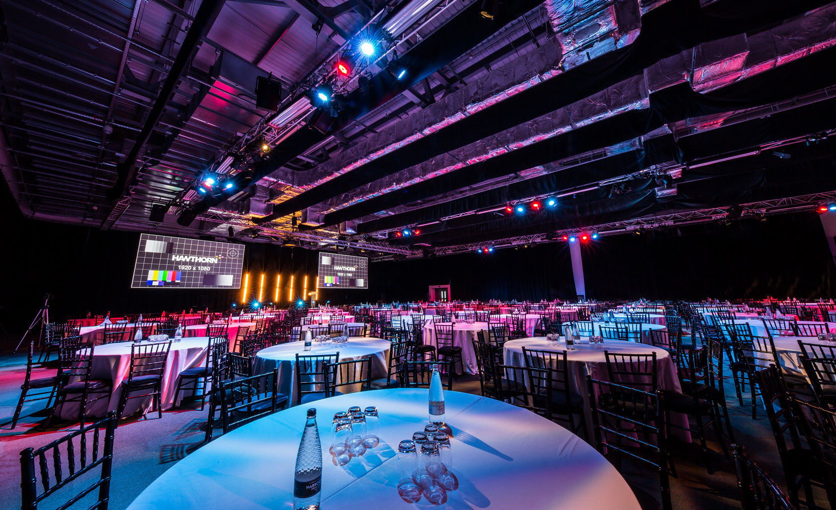 A large event Space with exposed piping and cabaret tables