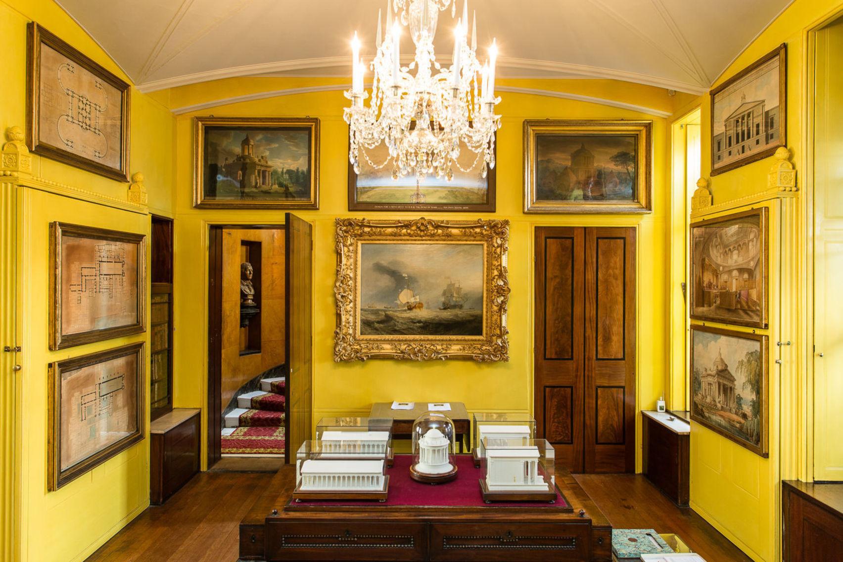 A yellow room with oil paintings on the walls and a large chandelier