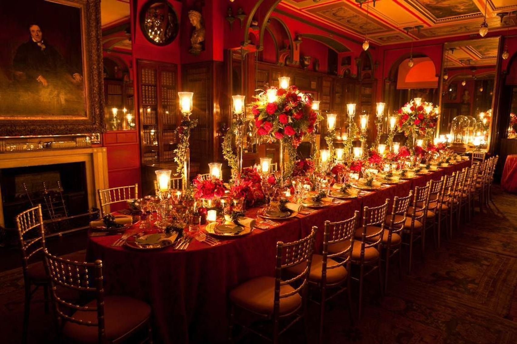A long private dining room covered in candles and red flowers