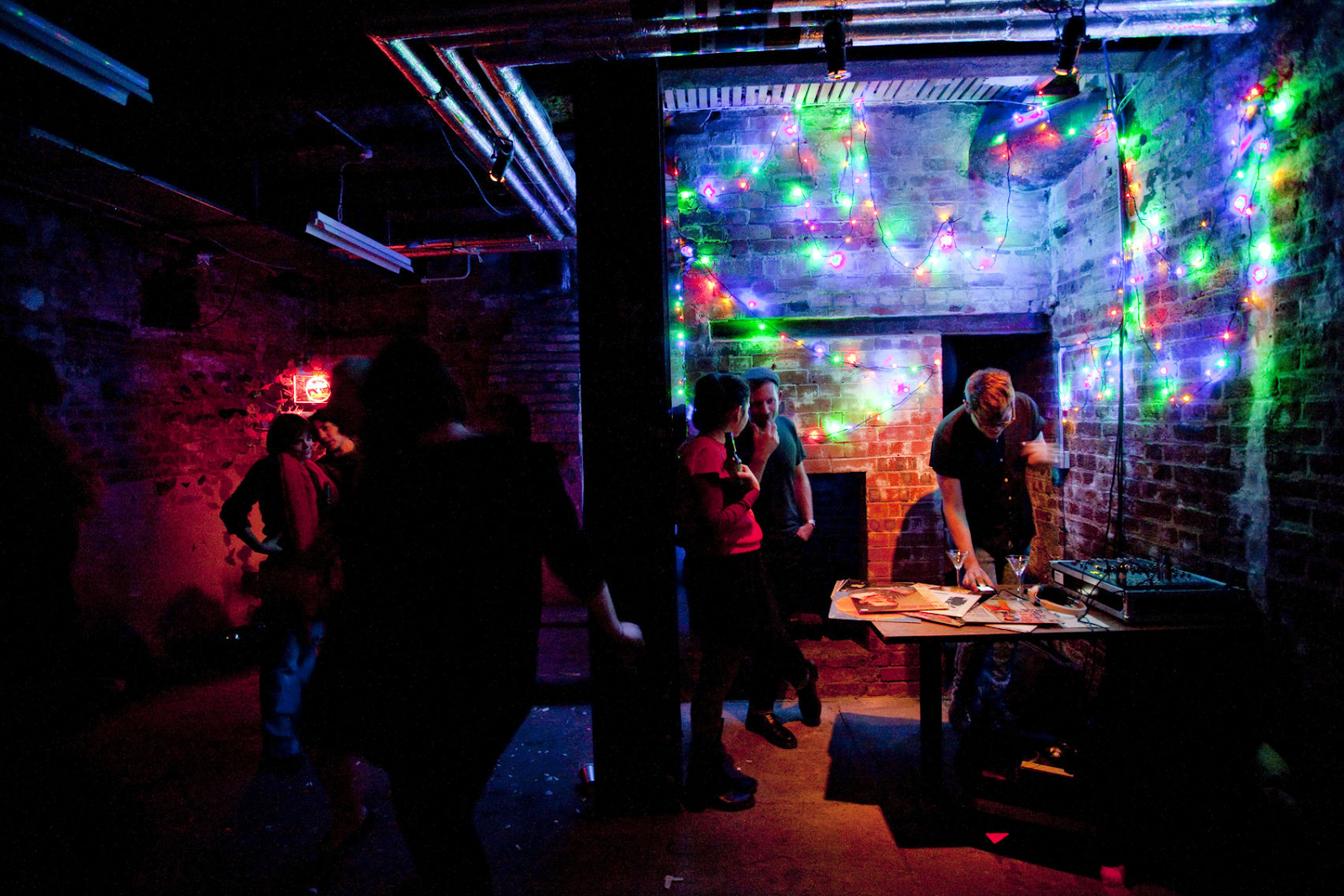 the ditch at shoreditch town hall is a dark underground bar with people in there.