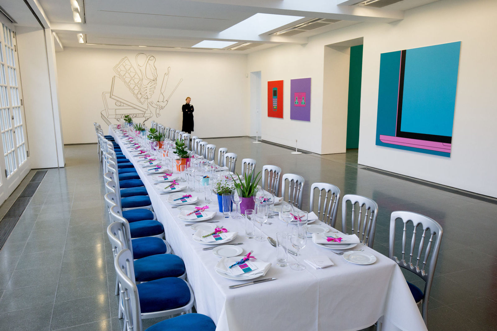 a large white room with a long white table set up for a private dining event