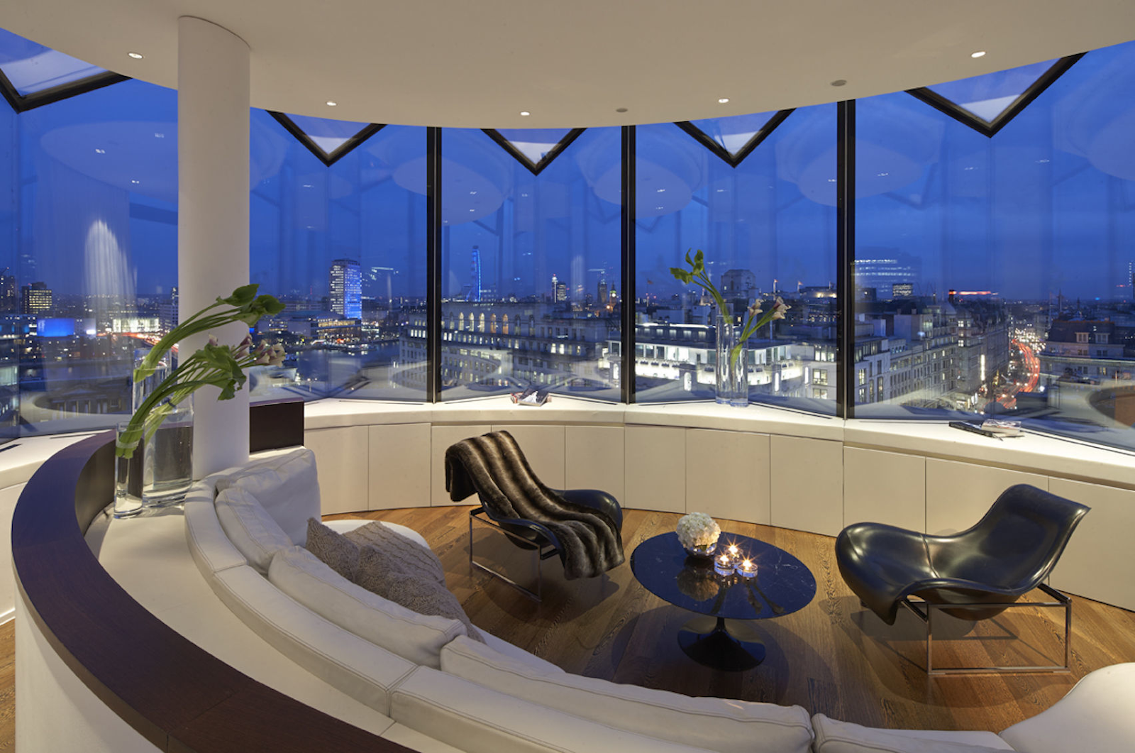a penthouse suite at ME London, with two black chairs set up facing each other. There is a large window overlooking London at nighttime