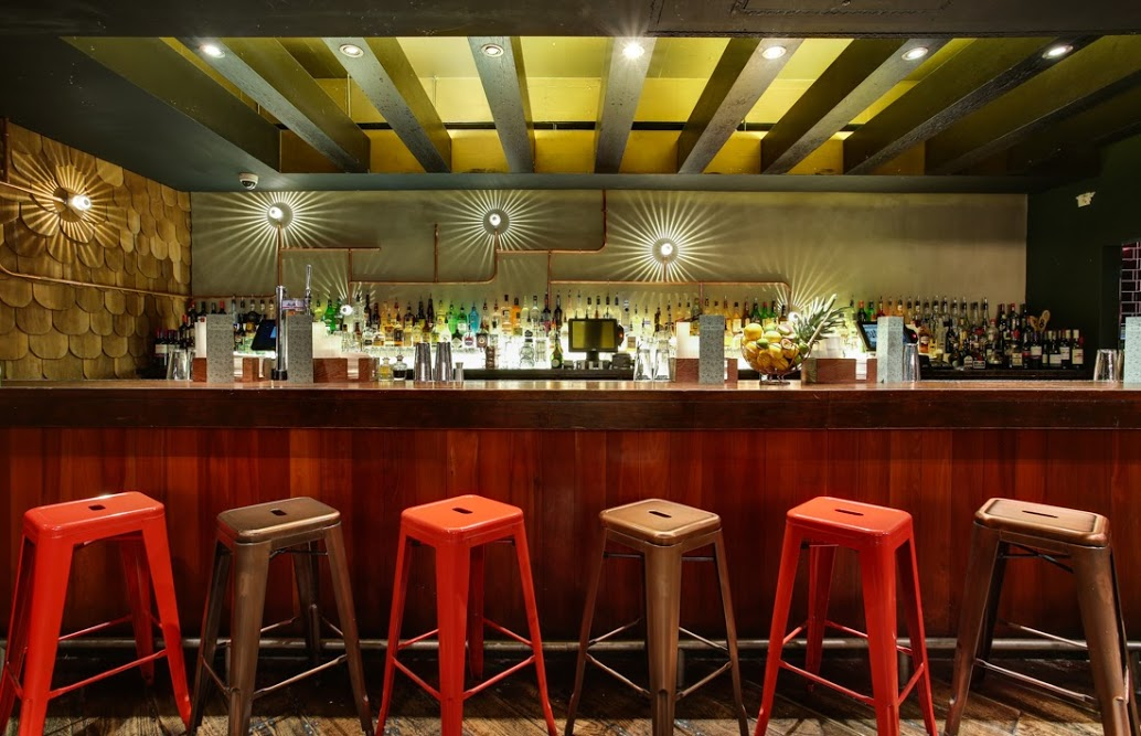 Christmas drinks venue in London showing a bar with bright lights and colourful bar stools