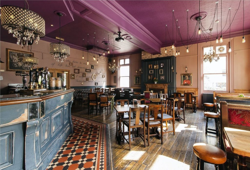 A restaurant space with a magenta ceiling, patterned tile flooring g and distressed blue bar.