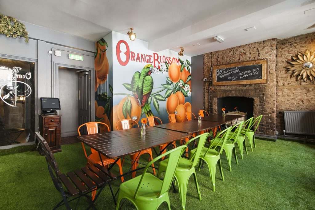 A dining room with green and orange chairs, green floors and oranges painted on the walls.