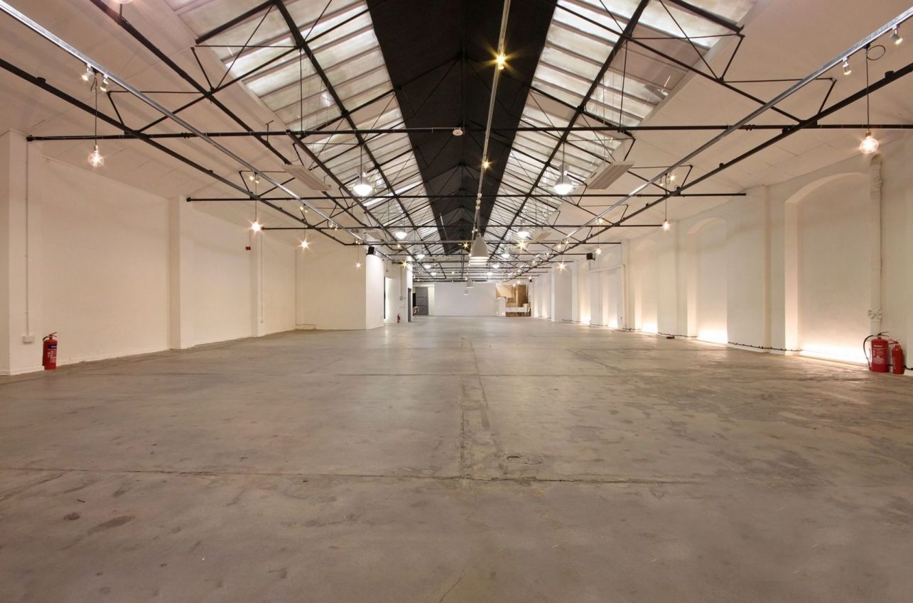 A huge victorian warehouse with black beams and spotlights
