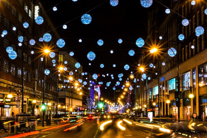 A busy London street at Christmas night time with lots of sparkling lights and bright headlights