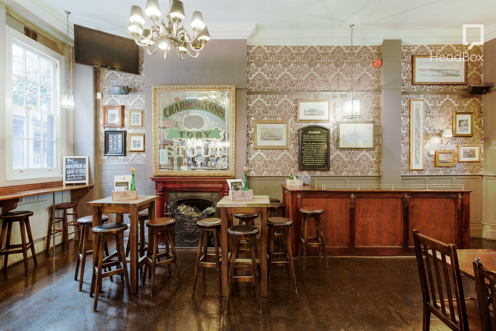 Well-lit bar with high wooden chairs and tables with patterned wallpaper and a decorated mirror on the back wall