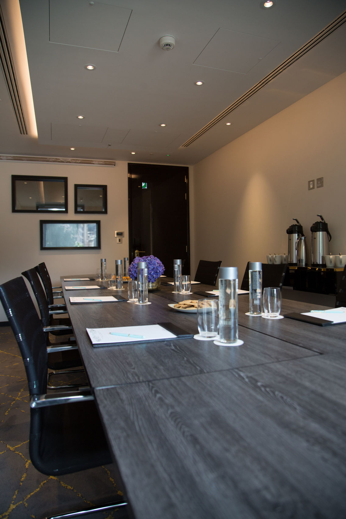 A meeting room with a long grey table