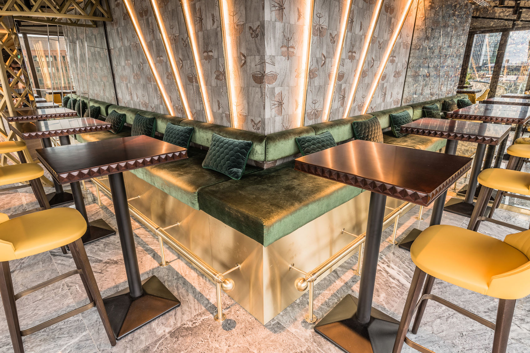 Tall copper tables and yellow chairs in the bar at Jin Bo Law