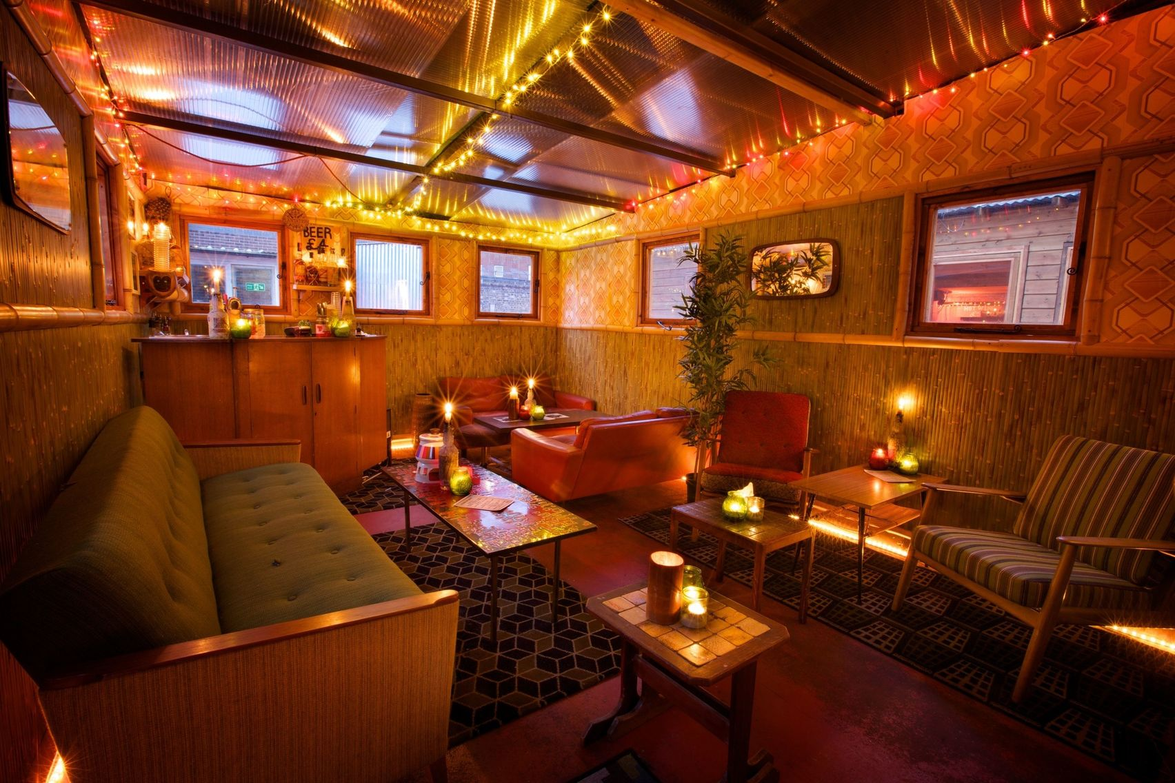 Christmas drinks venue with lots of seats and sofas with candles on the tables and orange and yellow fairy lights on the ceiling