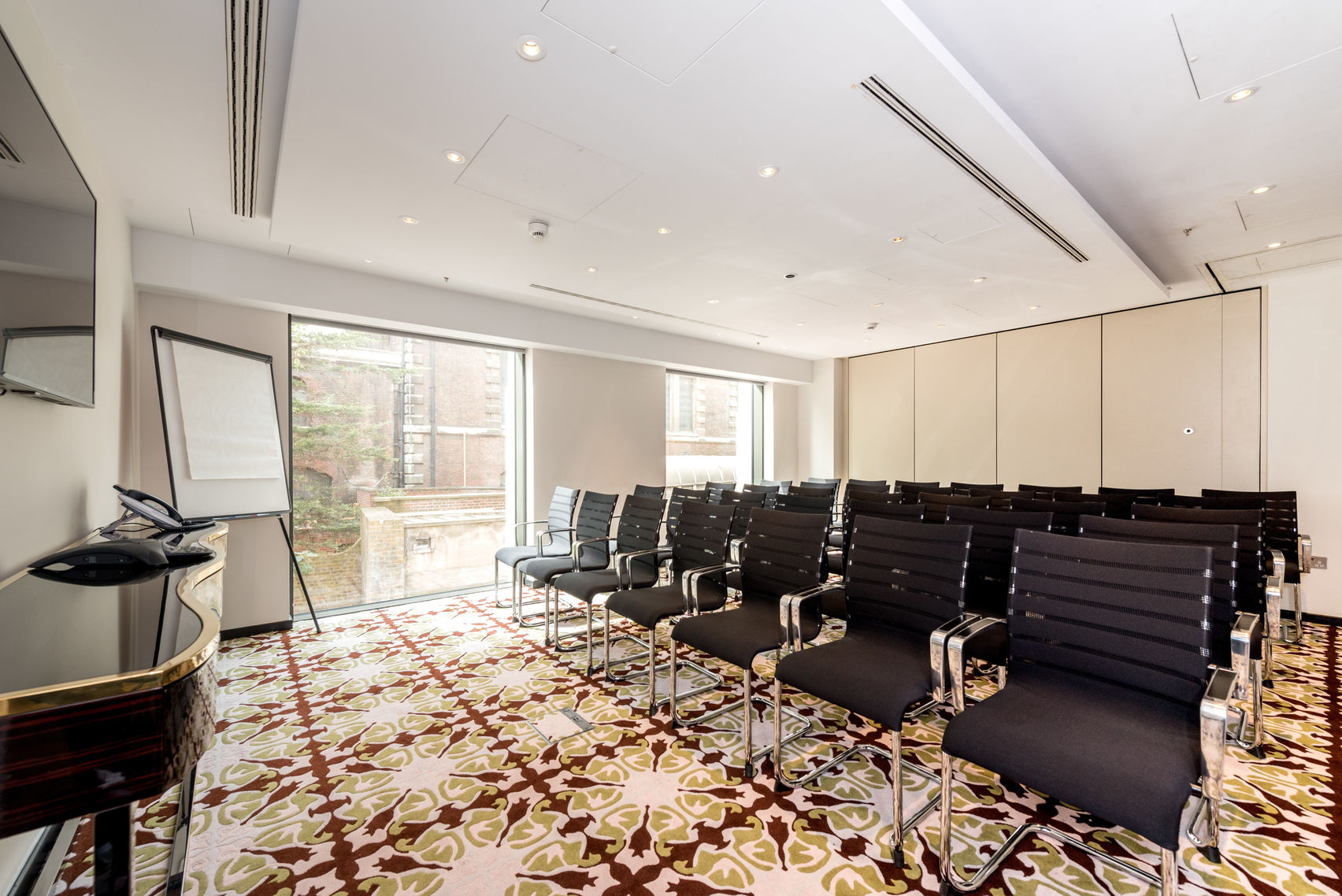 A bright meeting room with chairs facing a flip-chart with decorative red, cream and gold carpet