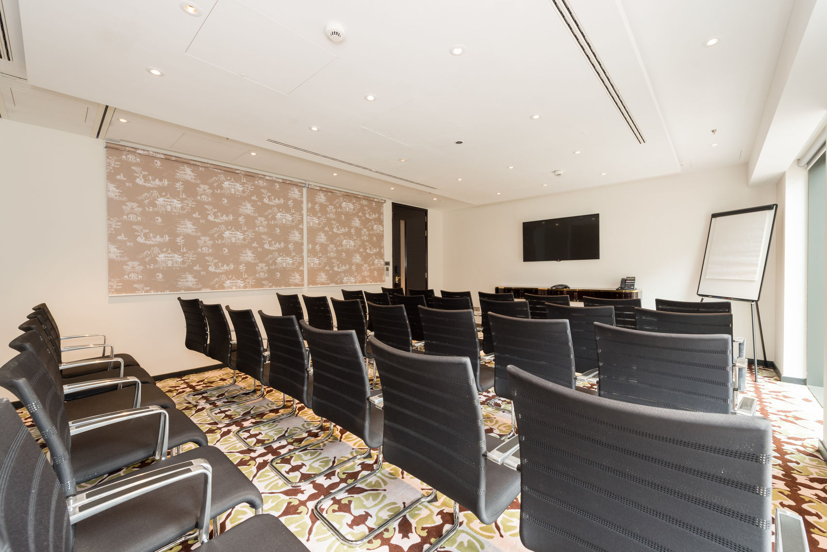 A room with lots of brown office chairs facing a flip-chart at the front of the room, with decorate red, gold and cream carpet