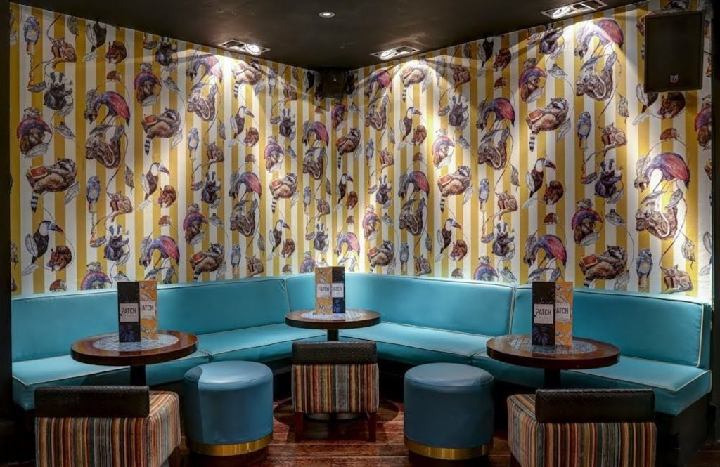 A bright blue corner sofa with three small wooden cocktail tables and a loud, patterned wallpaper as the backdrop
