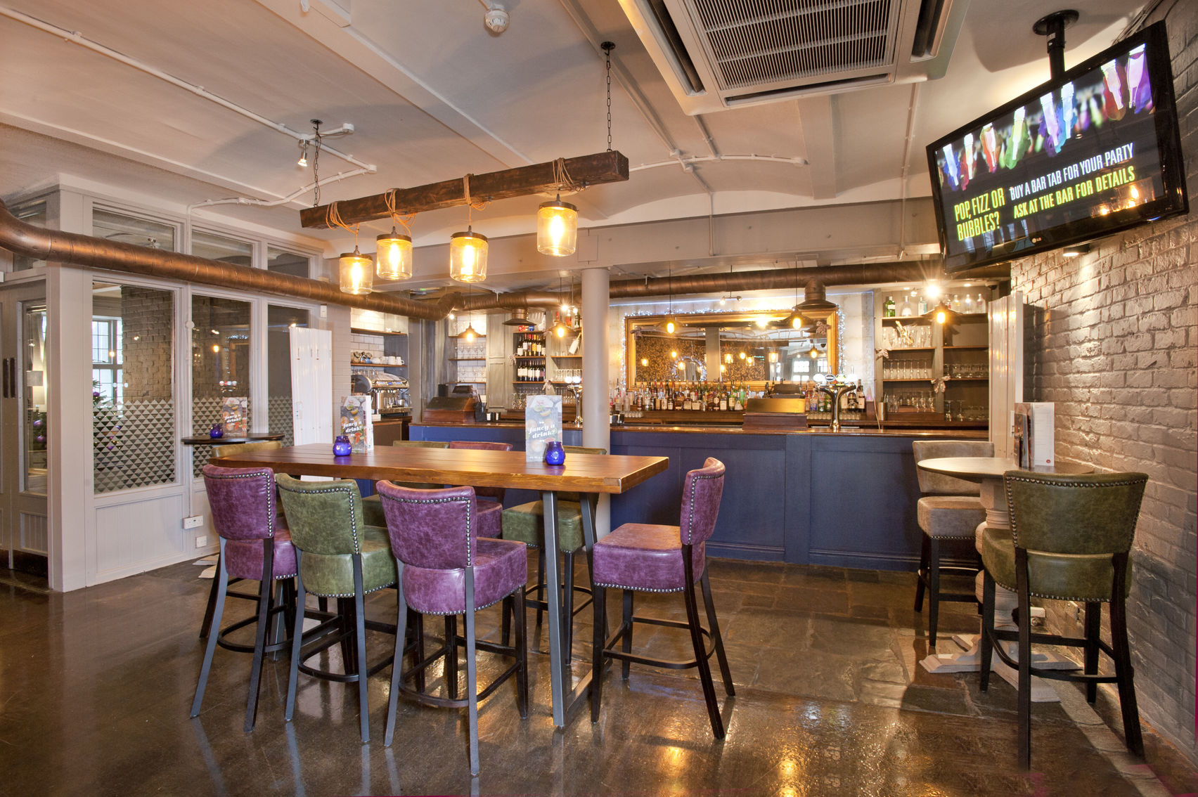 Purple and green chairs underneath four hanging lightbulb next to a bar and a tv screen
