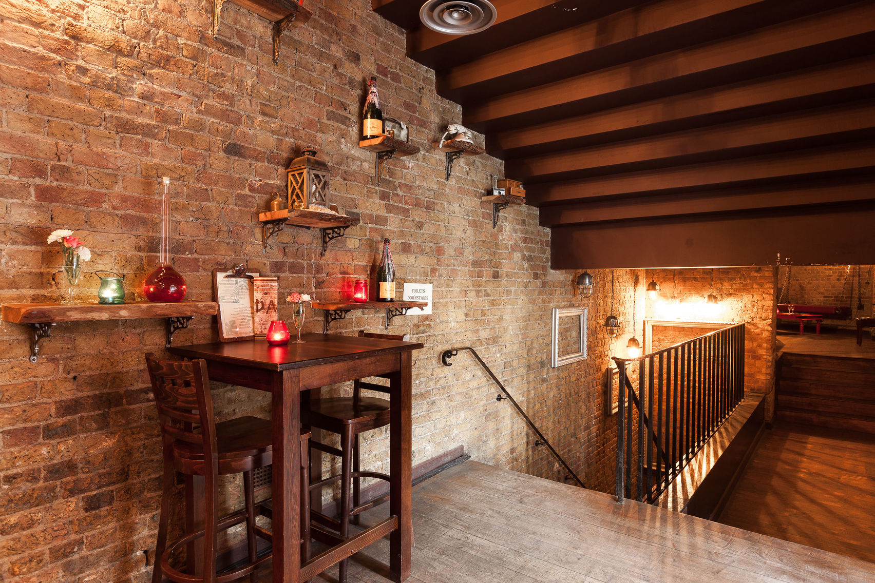 High wooden stools and a high wooden table with coloured glass candle holders next to a staircase and an exposed brick wall