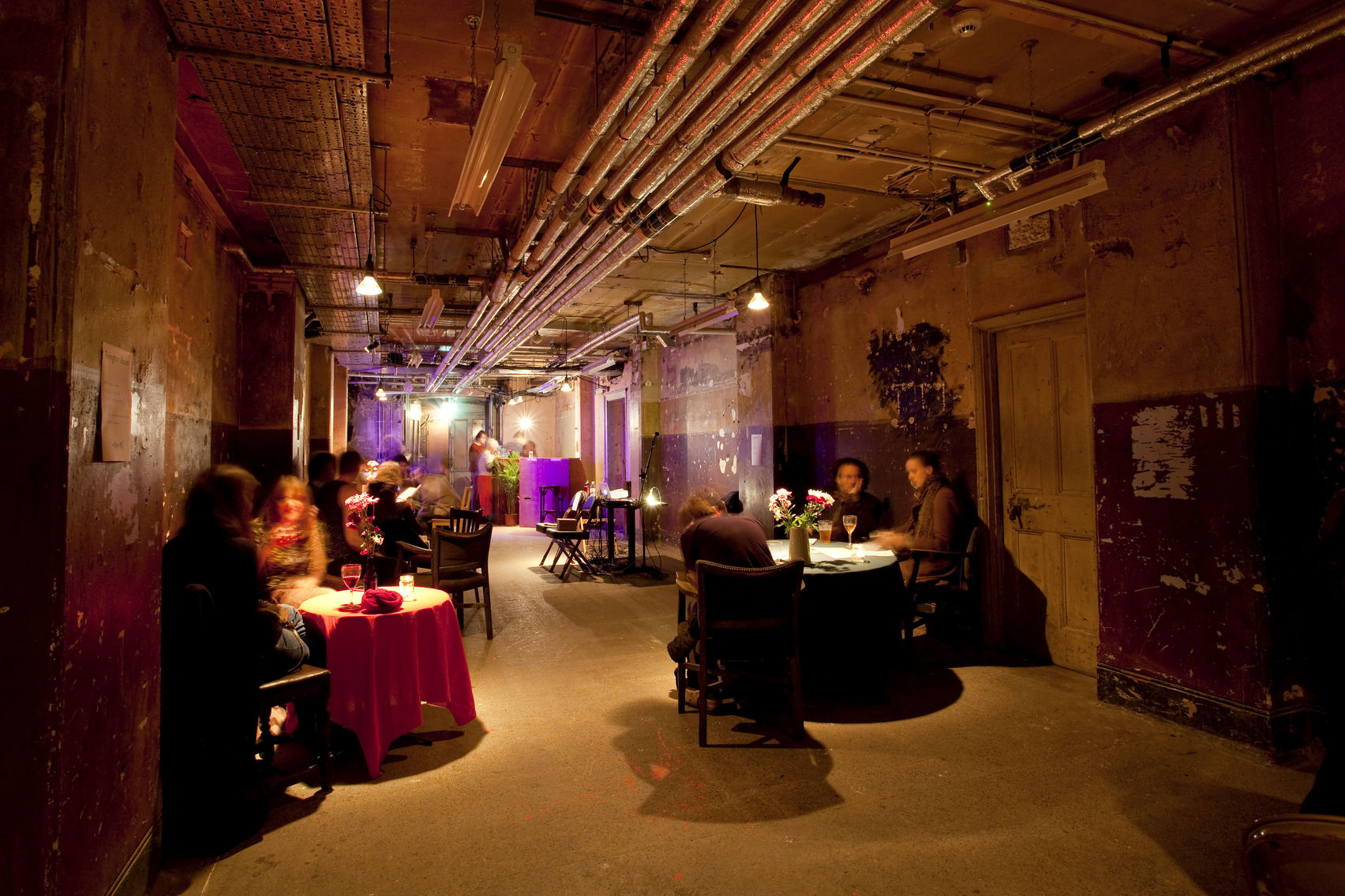 Underground basement bar with lots of tables with people eating and drinking and bright lights in the background