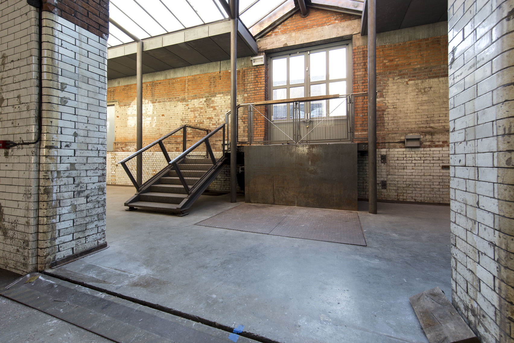 Metal staircase and window surrounded by exposed brickwork