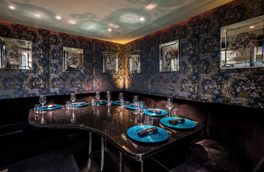 A dining room with a curved dark table, dark floral wallpaper and electric blue plates.