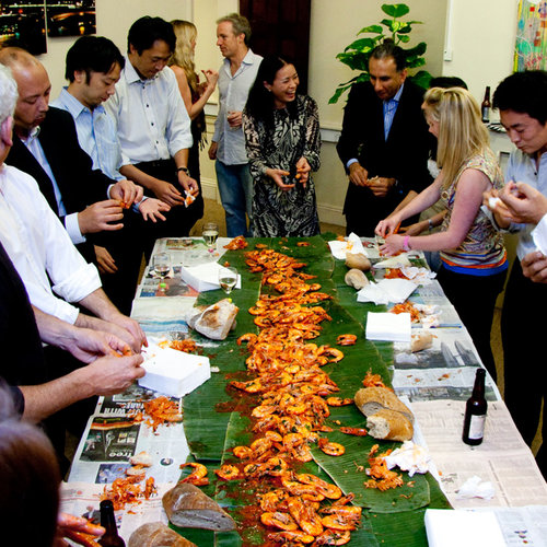 People stood around a long table which has palm leaves on with prawns on top.